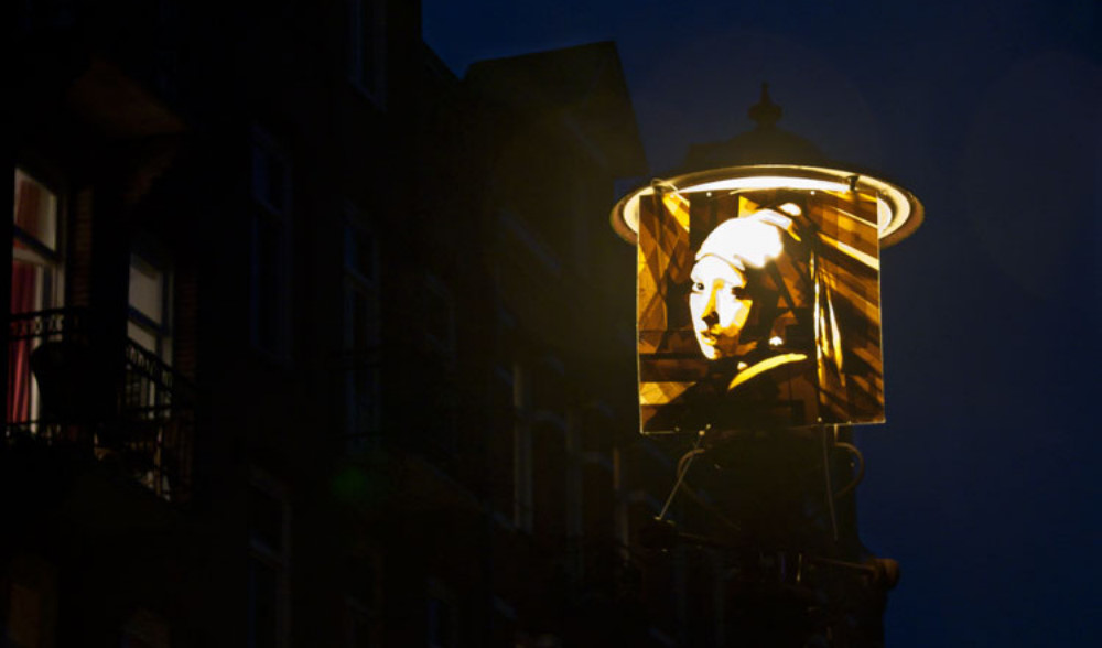 Artwork made of packing tape hung up on a street lamp in Amsterdam depicting the girl with the pearlearring, by Max Zorn. Kunst mit Klebeband, art du ruban