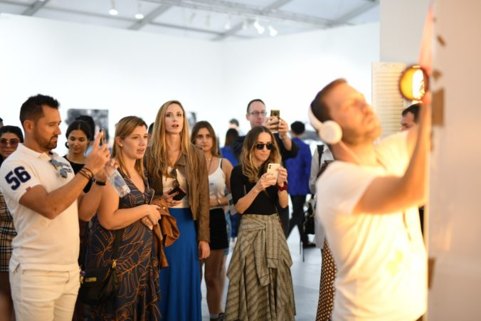Crowd of visitors admiring Max Zorn at work at the Scope art fair in Miami Beach during Art Basel Miami
